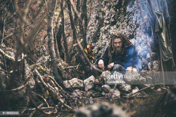 Young Man With Dreadlocks Sitting By a Fireplace in Nature