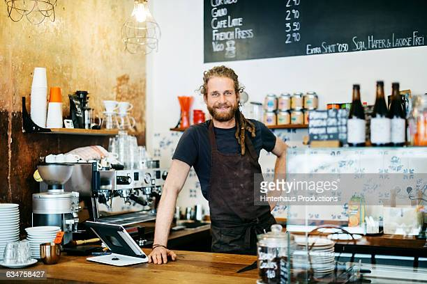 Young man with dreadlocks working as barista