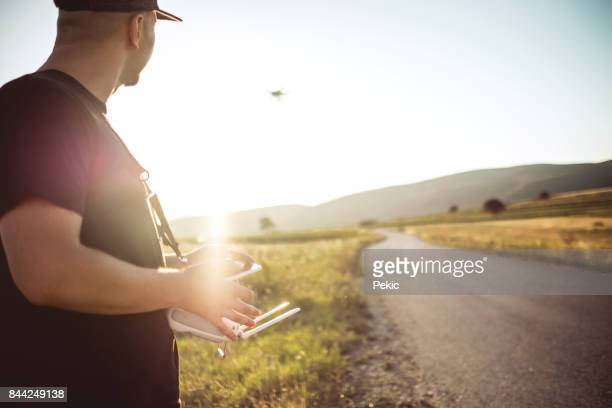 Young man with drone in sunset
