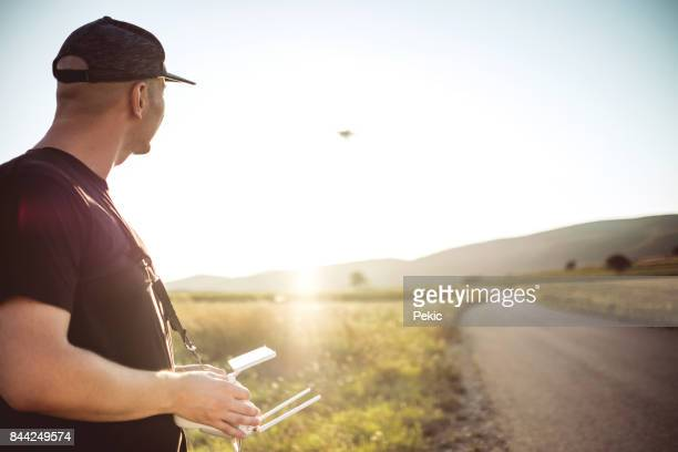 young man with drone in sunset - remote controlled stock photos and pictures
