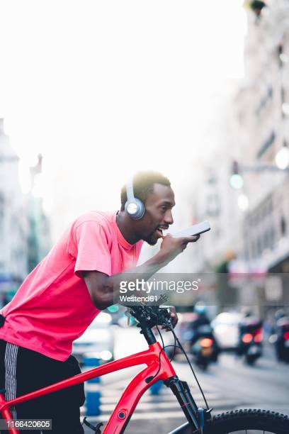 young man with e bike and headphones using smartphone in the city - vertical stock pictures, royalty-free photos & images