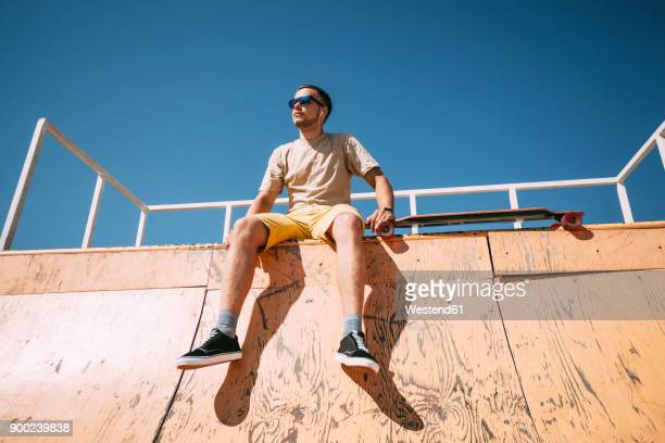 Young man with earbuds and longboard sitting on top of halfpipe in skatepark