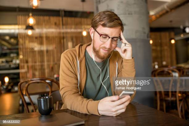 young man with earbuds using smartphone in a cafe - hoodie headphones stock pictures, royalty-free photos & images