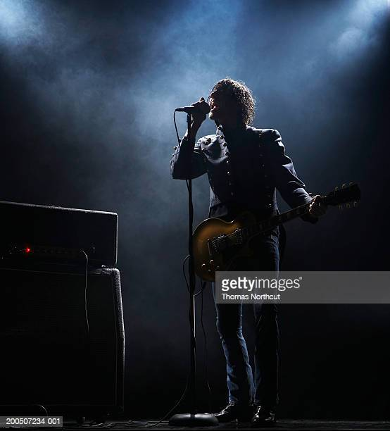 Young man with electric guitar singing into microphone on dark stage