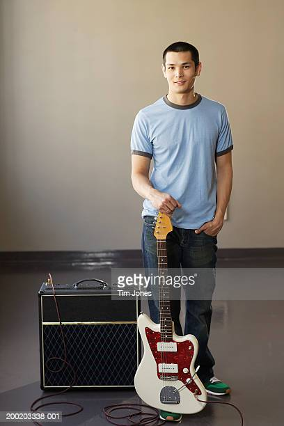 Young man with electric guitar standing beside amplifier, portrait