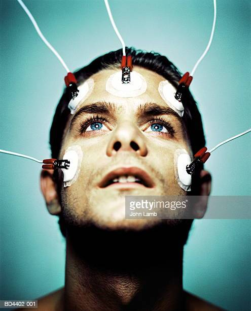 Young man with electrodes on face, close-up