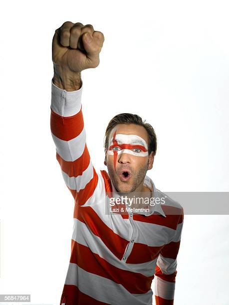 young man with english flag painted on face clenching fist - soccer body painting stock photos and pictures