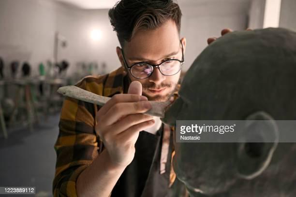 jovem com óculos esculpindo cabeça de barro - escultura - fotografias e filmes do acervo