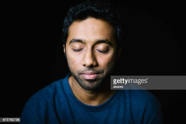 young man with eyes closed on black background - eyes closed stock pictures, royalty-free photos & images