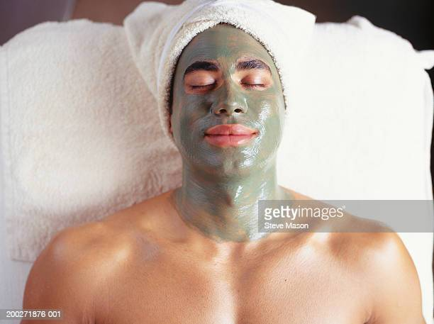 Young man with facial mask at beauty parlour, (overhead view
