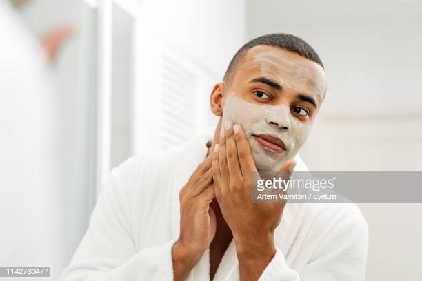 young man with facial mask looking in mirror at home - body care stock pictures, royalty-free photos & images