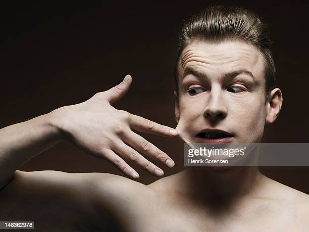 young man with finger glued to his face