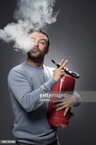 young man with fire extinguisher - fire extinguisher stock photos and pictures