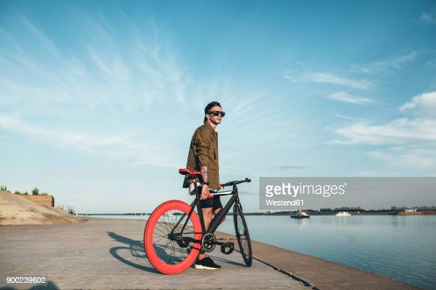 Young man with fixie bike at the waterfront