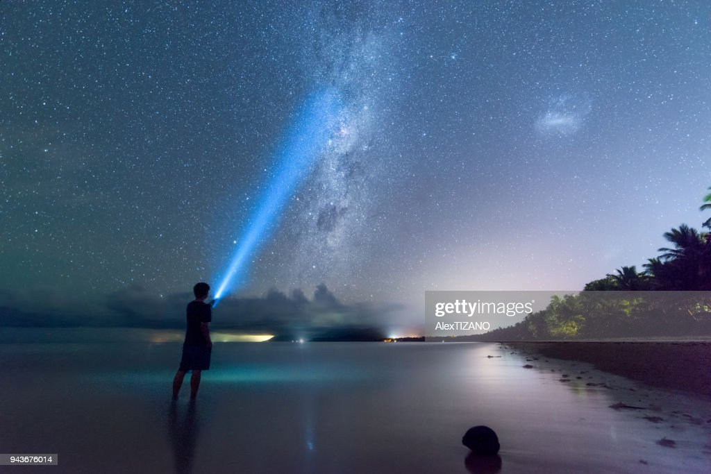 Young Man with Flashlight Stands on the Beach While Watching Galaxy , Cairns, Australia : Stock-Foto