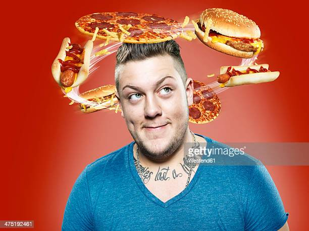 Young man with flying fast food around his head, Composite