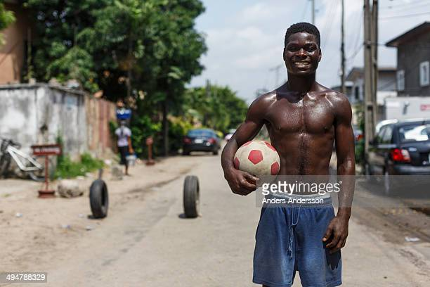 young man with football on street in Lagos.