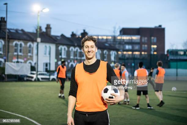 young man with football under arm smiling towards the camera with team mates in background - amateur stock pictures, royalty-free photos & images