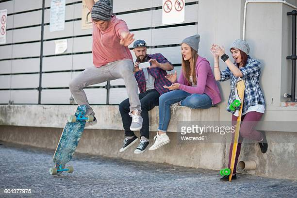 Young man with friends doing a skateboard trick