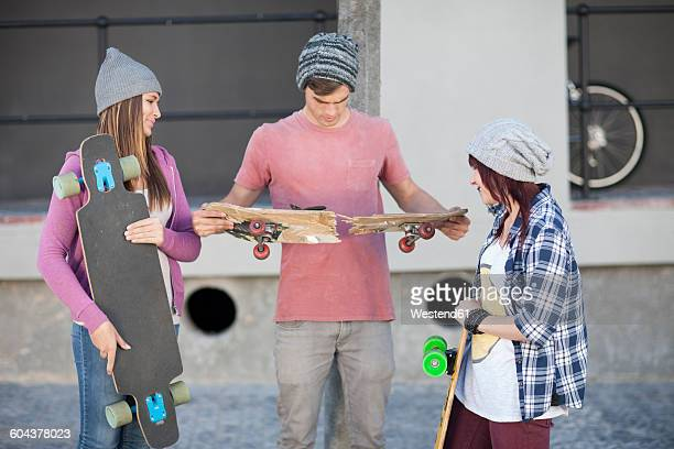 Young man with friends holding broken skateboard