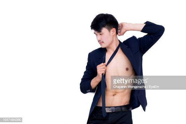 Young Man With Fully Unbuttoned Shirt Standing Against White Background
