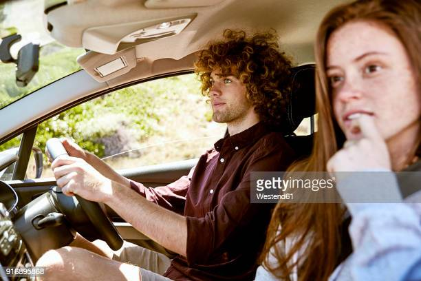 Young man with girlfriend driving car