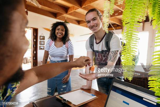 young man with girlfriend receiving keys on arrival at guesthouse - hostel stock pictures, royalty-free photos & images
