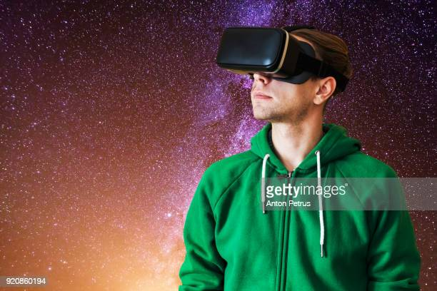 Young man with glasses of virtual reality on a background of night sky
