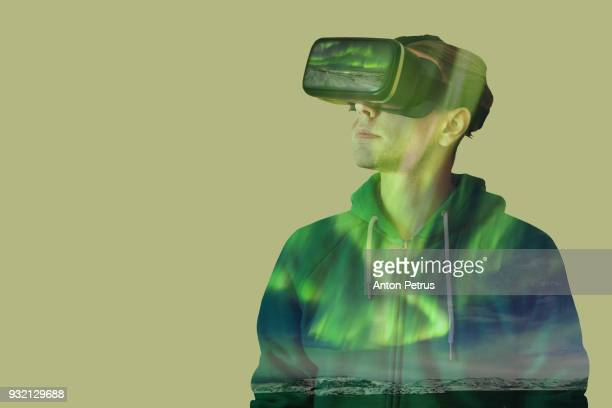 Young man with glasses of virtual reality on a background of northen lights