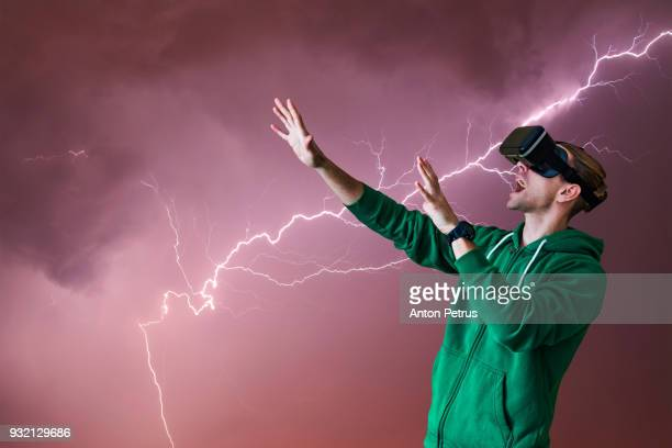 Young man with glasses of virtual reality on a background of thunderstorm