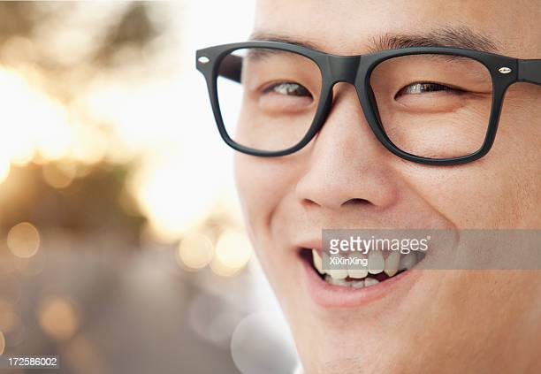 Young man with glasses smiling close-up