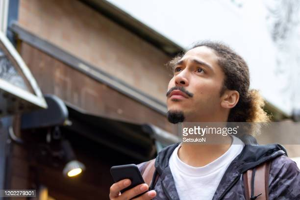 young man with goatee looking up in city street - goatee stock pictures, royalty-free photos & images