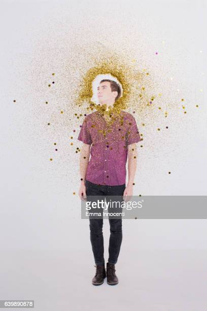 Young man with gold dust circling his head