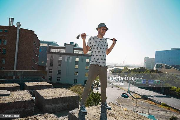 Young man with golf club looking over city, smiling