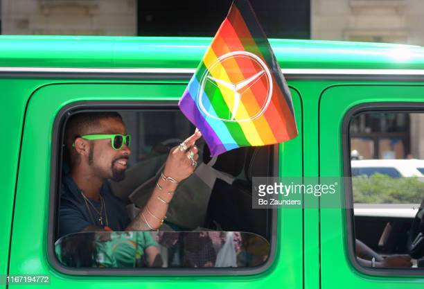 young man with green sunglasses in a green car, waving a rainbow flag at nyc pride march on june 30, 2019, in new york city. - pride stock pictures, royalty-free photos & images
