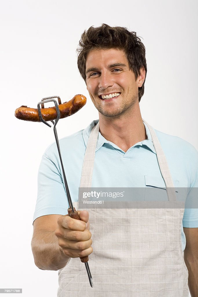 Young man with grilled sausage : Stock Photo