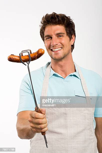 Young man with grilled sausage