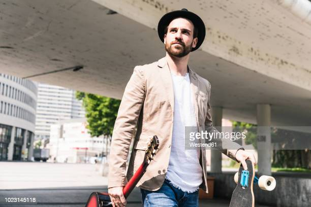 Young man with guitar and skateboard walking in the city