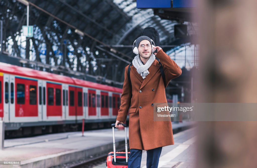 Young man with guitar case and headphones at station platform : Stock-Foto