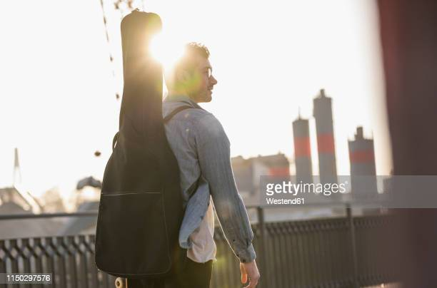 young man with guitar case in the city at sunset - guitar case stock pictures, royalty-free photos & images