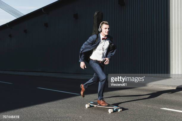 Young man with guitar case riding skateboard on the street