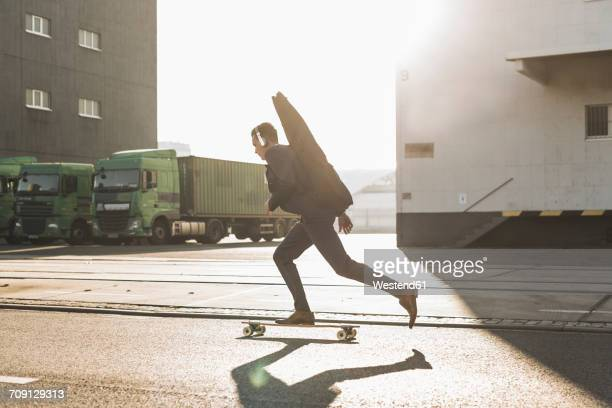 young man with guitar case riding skateboard on the street - distrito industrial - fotografias e filmes do acervo