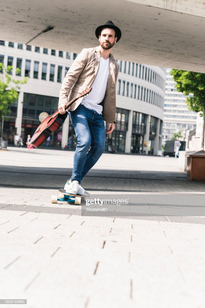 Young man with guitar riding skateboard in the city : Stock Photo