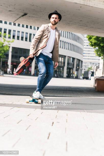young man with guitar riding skateboard in the city - maxim musician stock photos and pictures