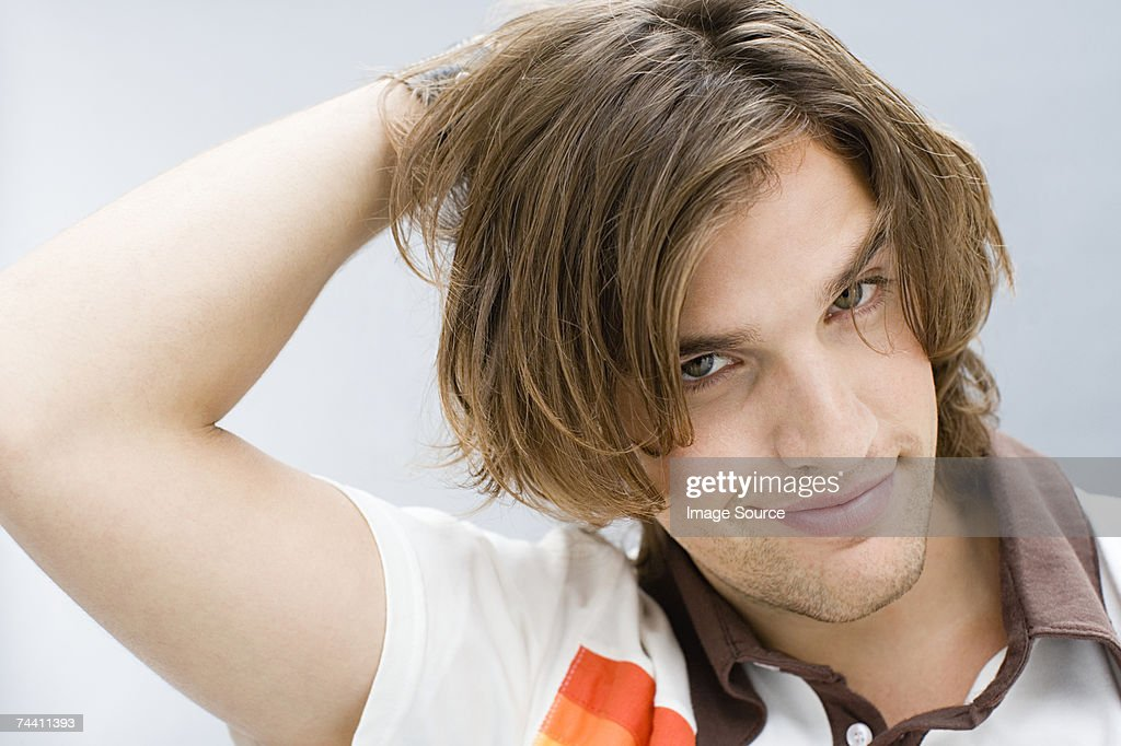 Young man with hand in hair : Stock Photo