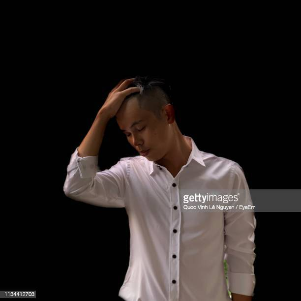 young man with hand in hair standing against black background - 髪に手をやる ストックフォトと画像