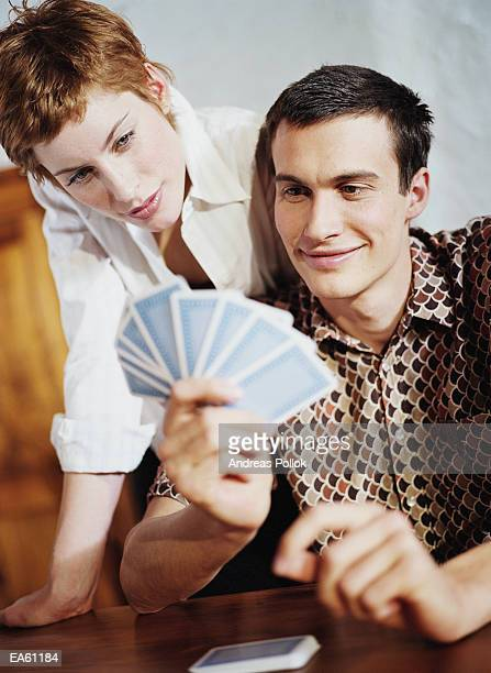 Young man with hand of cards, woman looking over man's shoulder