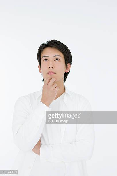 Young man with hand on chin, thinking