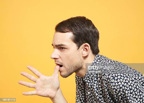 Young man with hand splayed from his mouth