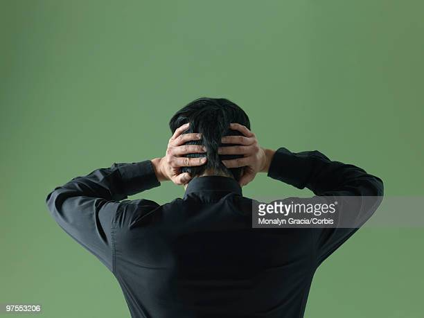 Young man with hands behind head